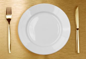 Golden knife, fork and white plate