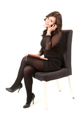 calling businesswoman with phone sitting on chair, full length