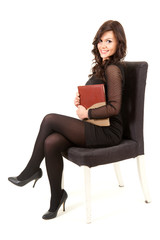 businesswoman sitting on chair with book, full length