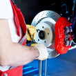 Motor mechanic is checking the brake of a car