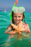 Snorkel girl with starfish in the sea
