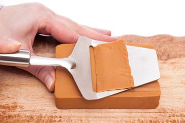 Hand tut Käse mit Käsehobel hobeln