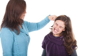 mother pulling her daughter's ear and punishing her