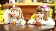 Two girls drinking juice and looking at camera