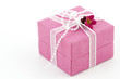 Pink giftbox with a ribbon and a little flower