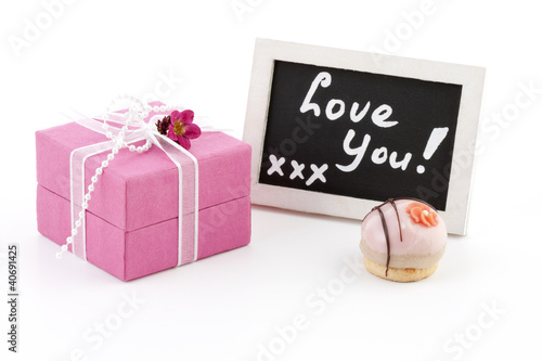 """Pink present and a chalckboard with the words """"love you"""""""