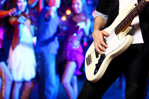 Young guitar player performing in night club