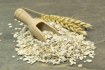 A small heap of oatmeal flakes with wooden scoop
