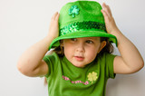 Pretty little girl tries on a fancy hat for St. Patrick's Day - 40694400
