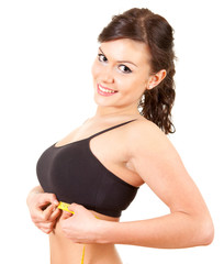 young woman measuring her under breasts, white background