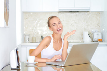 Laughing woman sitting at laptop computer
