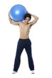 Young bodybuilder exercising with fitness ball in gym