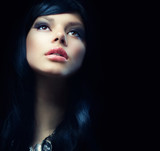 Beautiful Brunette Girl over Black Background. Darkness