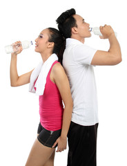 man and woman drinking water after fitness