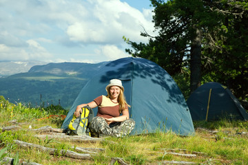 female hiker sitting    near camp tent