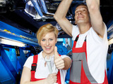 Happy apprentice and assembly operators in a garage