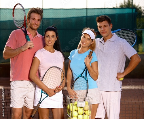 Attractive couples on tennis court smiling