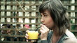 Happy woman drinking juice in outdoor bar, steadicam shot