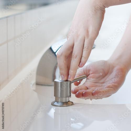 Washing hands in a public restroom - applying soap