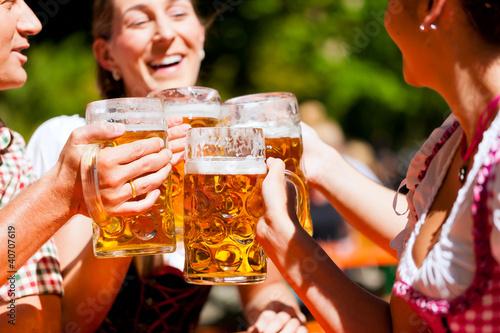 Zwei glückliche Paare sitzen im Biergarten