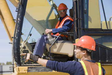 Two engineers operating an earth mover