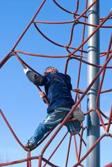 Junge hängt in den Seilen