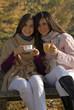 Amigas disfrutando de un café en otoño.