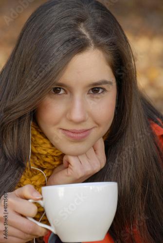 Joven mujer bebiendo café en otoño.