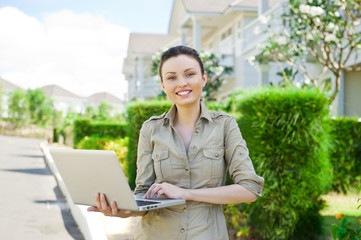 Female realty agent with laptop presenting beautiful house