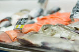 Fresh red sliced fish lie on table with ice in supermarket