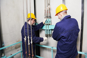 machinists adjusting lift in elevator hoistway