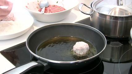 Cocinera friendo albondigas en aceite de oliva