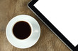 Touch screen device and cup of coffee on old wooden background
