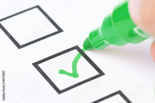 Macro shot of human hand drawing green check mark in checklist b