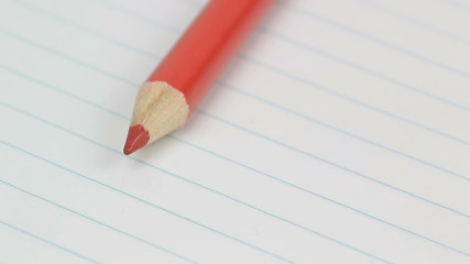 Orange pencil in lined paper