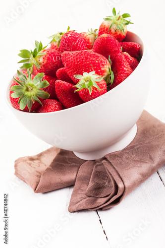 Strawberries inside bowl on white table