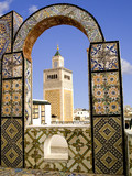 Mosque minaret framed by a tiled arch in Tunis city, Tunisia