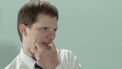 Stressed adult businessman biting fingernails