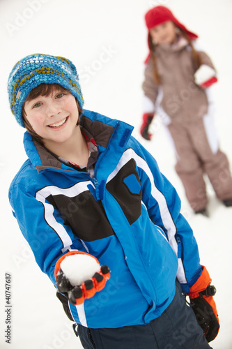 Two Young Children Having Snowball Fight Wearing Woolly Hats