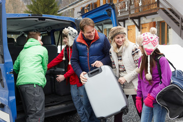 Family Unloading Luggage From Transfer Van Outside Chalet On Ski