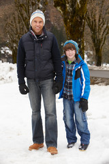 Father And Son Walking Along Snowy Street In Ski Resort
