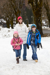 Mother Walking Two Children To School Along Snowy Street In Ski