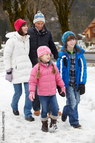 Family Walking Along Snowy Street In Ski Resort