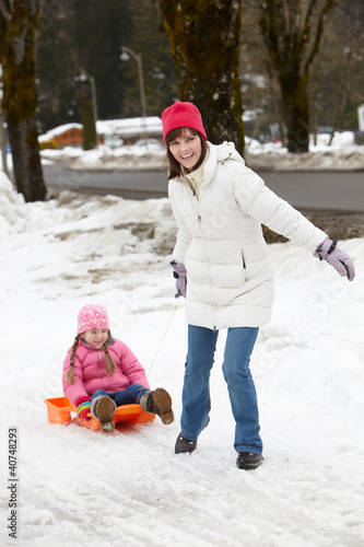 Mother Pulling Daughter On Sledge Along Snowy Street In Ski Reso
