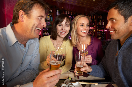 Group Of Friends Enjoying Sushi In Restaurant