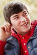 Teenage Boy Wearing Earphones And Listening To Music Wearing Win