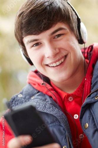 Teenage Boy Wearing Headphones And Listening To Music Wearing Wi