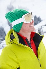 Young Man On Ski Holiday In Mountains