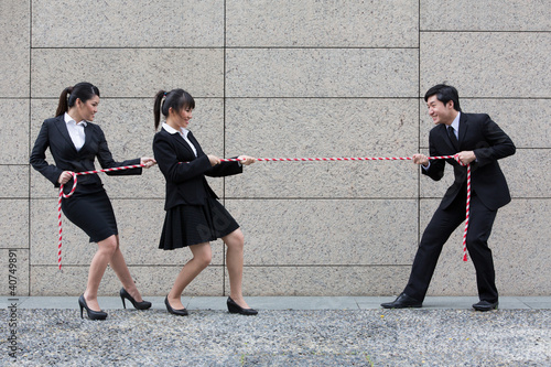 Business people having a tug of war fight.