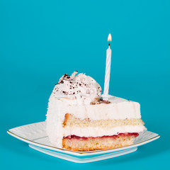 Piece of birthday cake with a candle
